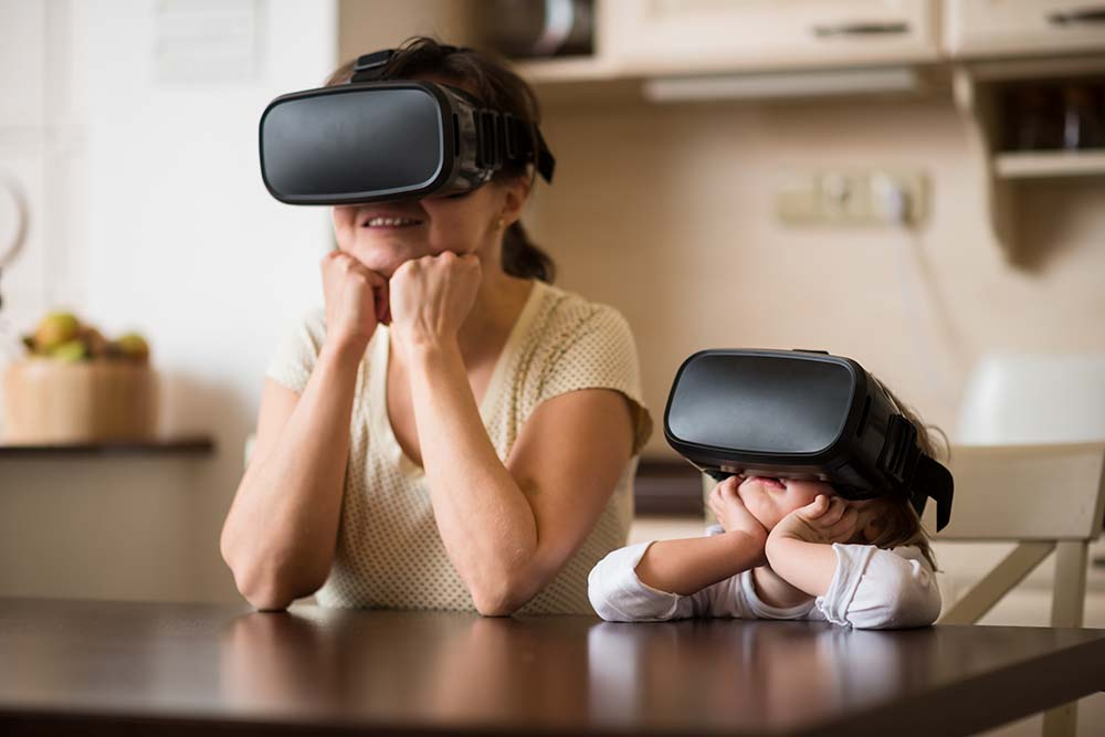 Mother and child together with virtual reality headsets indoors at home